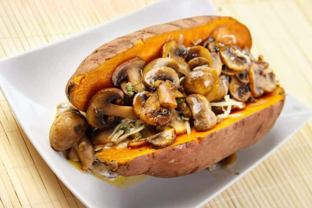 *** Local Caption *** Oven cooked sweet potato , filled with mushroom sauce and roasted champignons